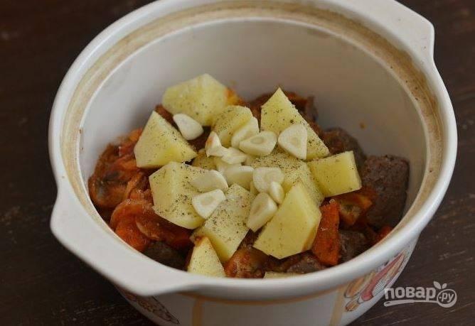 Картофель очистите и вымойте. Нарежьте его крупными кусками и положите к остальным ингредиентам. Чеснок почистите и нарежьте пластинками. Выложите на картофель, посолите и поперчите блюдо.