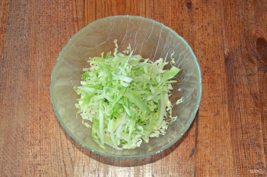 В глубокий салатник нашинкуйте капусту.