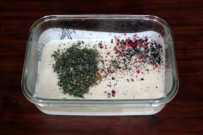В первую очередь приготовьте маринад. Для этого в достаточно глубокой емкости смешайте кефир, измельченные перцы, а также сушеный базилик.