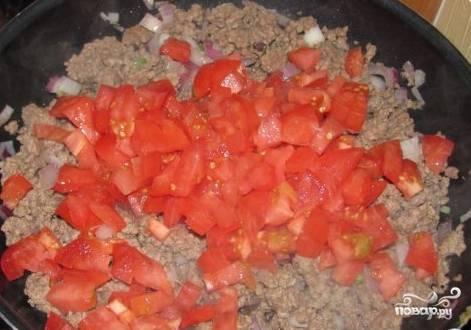 Обжарьте фарш с луком. За пару минут до готовности добавьте нарезанные кубиками томаты. Хорошо размешайте.