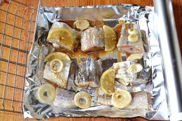 На решетку выложите фольгу, распределите кусочки минтая с лимоном и луком.