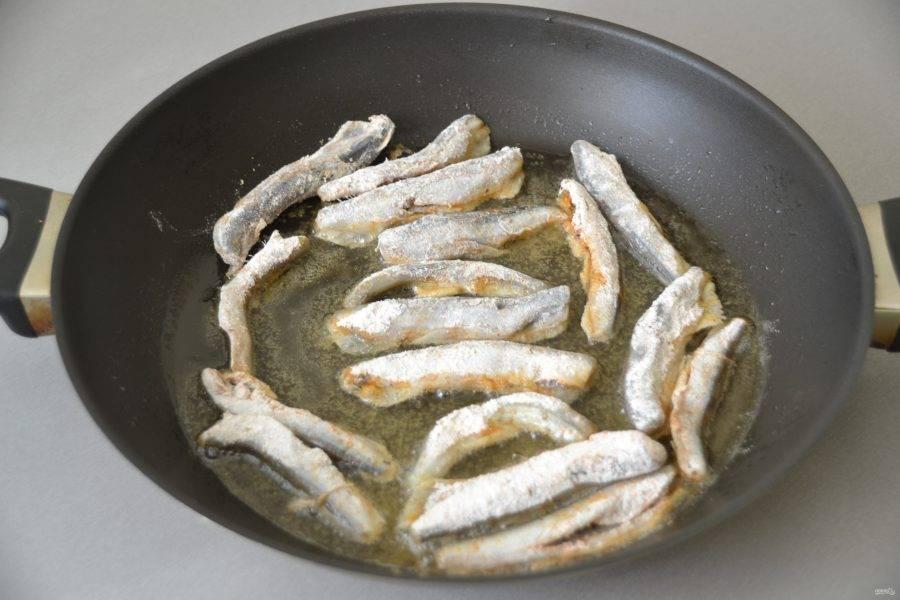 На сковороду влейте растительное масло и как следует его разогрейте, затем выкладывайте рыбу, не слишком плотно.