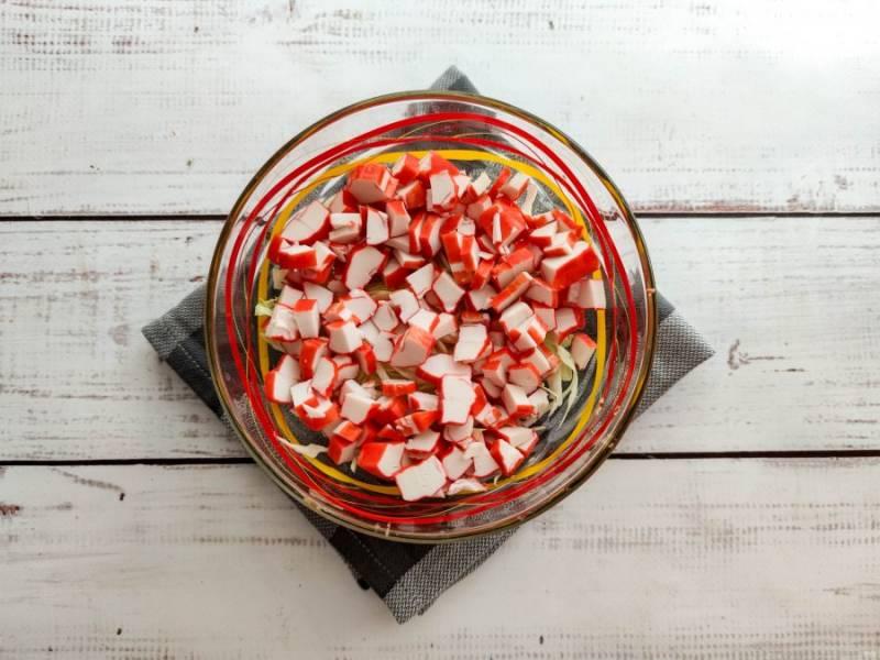 Крабовые палочки мелко нарежьте и добавьте к капусте.