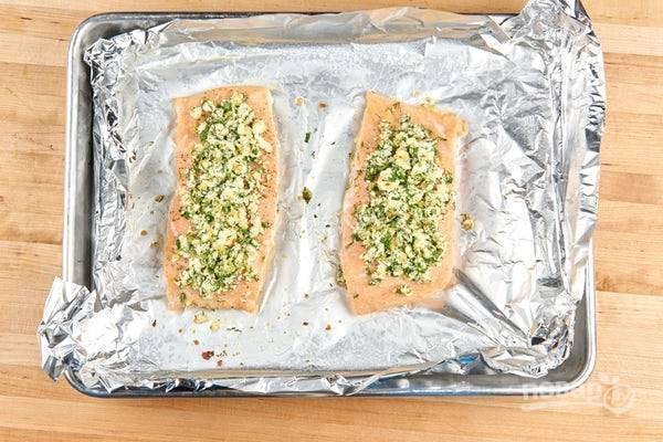 4. Теперь займитесь рыбой. На противень выложите лосося. Сверху распределите кусочки сыра, петрушку, цедру и половину чеснока. Запекайте лосося в течение 10 минут в духовке при 180 градусах.