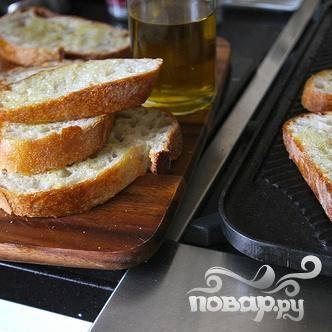 5. С помощью кисти смазать 2 столовыми ложками оливкового масла обе стороны ломтиков багета. Обжарить в сковороде  на среднем огне или в духовке в течение 1 ½-2 минут с каждой стороны, пока не подрумянятся. Натереть каждый ломтик хлеба долькой чеснока.