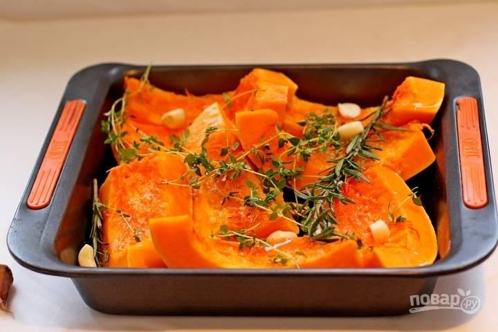 1. Тыкву вымойте, нарежьте и выложите в жаропрочную форму. Полейте маслом, подсолите, добавьте чеснок и специи. Отправьте в разогретую до 180 градусов духовку.