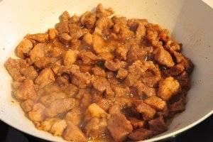 Спустя 20 минут, когда мясо станет достаточно мягким, испарится выделившийся сок и кусочки начнут зарумяниваться, нужно добавить 2 ст. л. винного уксуса и 3 ст. л. соевого соуса, перемешать, накрыть крышкой и жарить ещё 3 минуты.