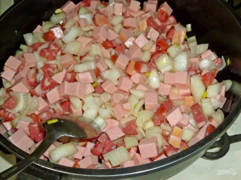 5. Нарезаем соленые огурцы и добавляем к колбасе. Жарим при постоянном помешивании.