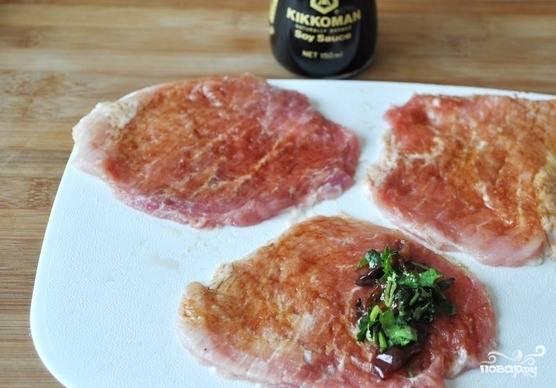 Свинину зачистите, вымойте и обсушите. Нарежьте на медальончики размером в один сантиметр. Заверните в пищевую пленку и отбейте молотком. Затем смажьте их с одной стороны соевым соусом. Выложите на мясо начинку из сковородки, сверните мясо трубочкой.