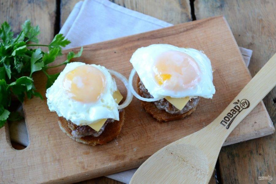 Приготовьте яичницы любым удобным для вас способом. Как это делаю я: хорошо разогреваю сковороду, разбиваю яйца, немного солю, накрываю крышкой и уменьшаю огонь до минимума. Жарю несколько минут, пока белок на желтке слегка не побелеет. Очень важно оставить желток жидким. Готовое яйцо положите на чизбургер.