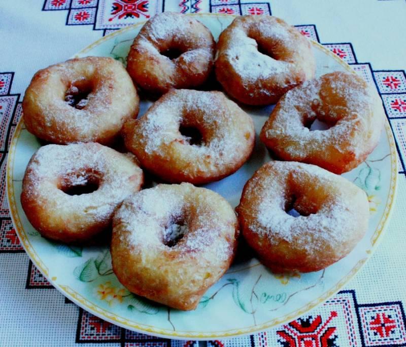 Готовые пончики выкладываем на тарелку, выстланную салфетками. Это нужно для того, чтобы с пончиков сошло лишнее масло. Из 100 граммов сахара делаем сахарную пудру с помощью кофемолки, либо ступкой. Можно взять уже готовую сахарную пудру. Посыпаем стекшие пончики с двух сторон. Подаем с чаем, кофе или молоком. Приятного аппетита!