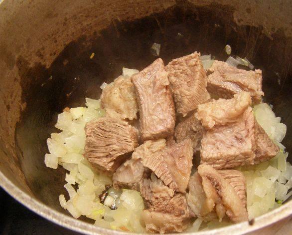 Из бульона извлекаем мясо и добавляем его к луку. Готовим 15-20 минут под крышкой.