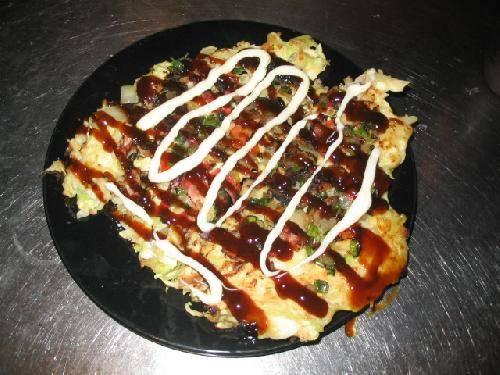Выкладываем блюдо на широкую тарелку и щедро поливаем соусом Okonomiyaki и майонезом.