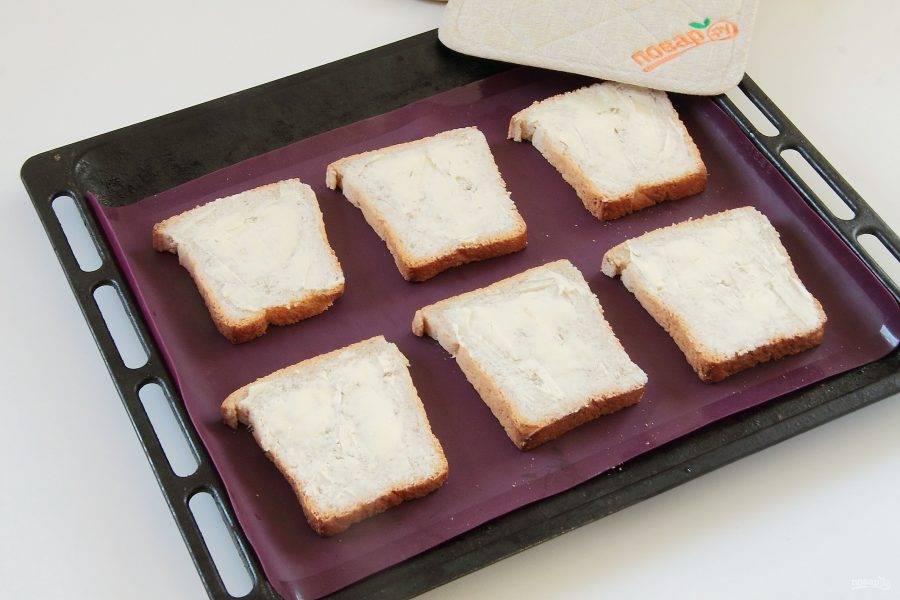 Смажьте хлеб с одной стороны маслом и выложите на противень.