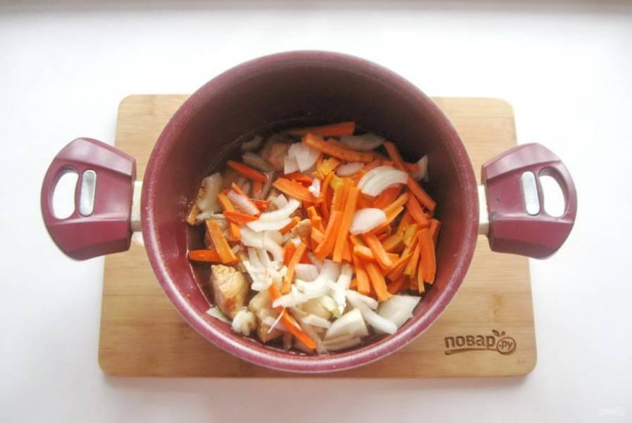 Морковь и лук очистите, помойте. Морковь нарежьте соломкой, а лук полукольцами. Добавьте в кастрюлю с мясом.