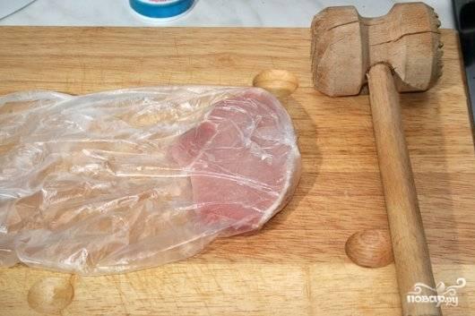 Теперь каждый кусок нужно прикрыть пищевой пленкой и отбить молотком. Не сильно, но так чтобы нарушить структуру волокон - мясо станет мягче.