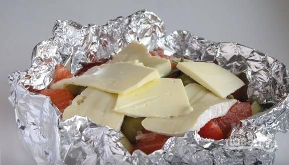 Выложите подготовленные рыбу и овощи в импровизированную посуду, которую следует изготовить из фольги, свернутой в несколько раз. Присыпьте овощи солью, перцем, положите сверху по кусочку масла и добавьте немного розмарина. Затем положите кусочки камамбера.