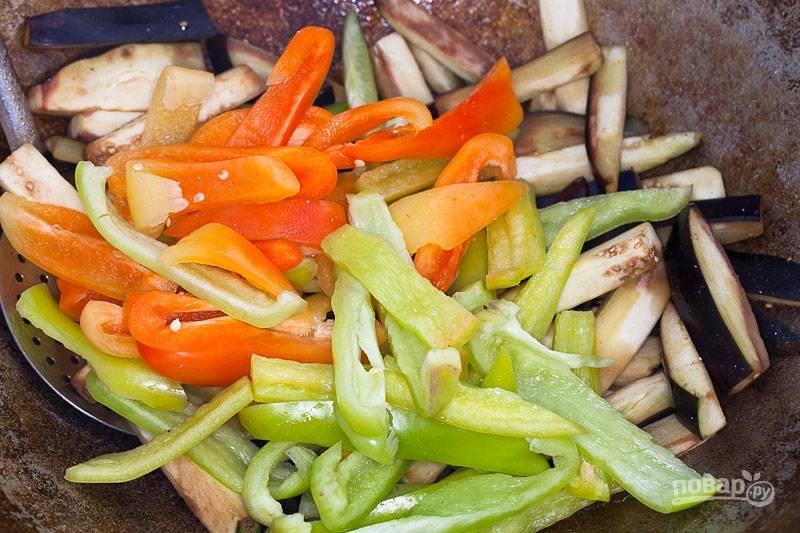 Уберите из казана морковь с луком. Теперь в нём готовьте перец и баклажан (крупными кусками). Не забудьте влить масло.