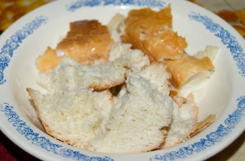 Для начала нам необходимо разломать белый хлеб на небольшие кусочки, выложить в миску и залить молоком. Через 10 минут, когда хлеб размокнет, отжимаем его и перекладываем в чистую миску.