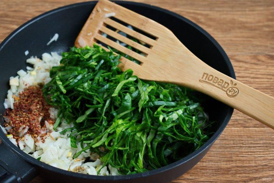 Добавьте красный жгучий перец, сушеную паприку, мелко нарезанный шпинат, перемешайте. Готовьте в течение 3 минут.