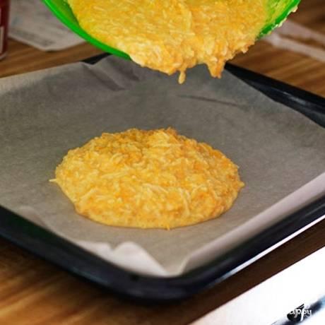 Сперва приготовим сырное тесто. Для этого смешаем тертый сыр, майонез, взбитые венчиком яйца и муку. Половину теста равномерно распределяем по противню, застеленному пергаментной бумагой.