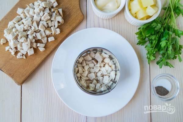 Остывшую куриную грудку нарезаем на мелкие кусочки. И с помощью кольца начинаем формировать салат. Первым слоем выкладываем куриное мясо, посыпаем перцем и слегка смазываем его майонезом.