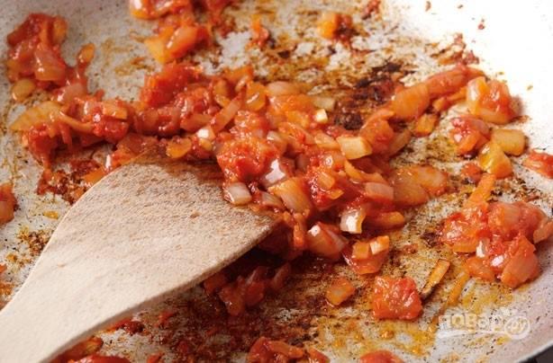 В другой сковороде обжарьте измельчённый лук вместе с томатным пюре и маслом в течение 10 минут. Не забывайте мешать.