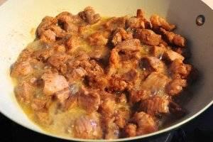 Когда свинина начнёт выделять сок, накройте её крышкой и немного убавьте огонь.