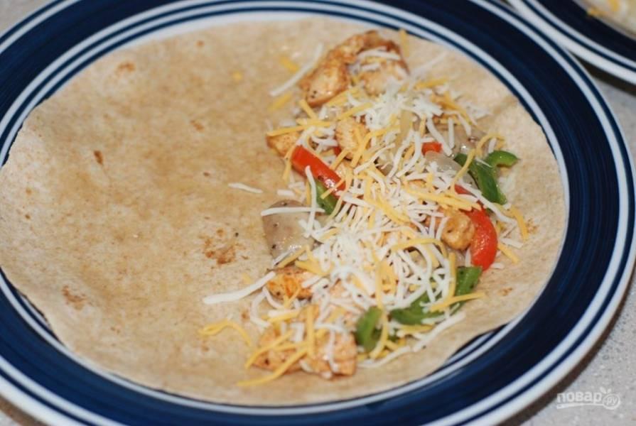 3. Подогрейте тортилью на сковороде и поместите на одну половину немного мяса, овощей и тертого сыра.