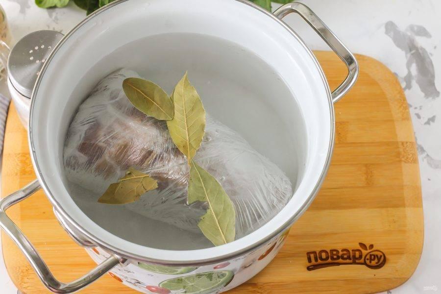 Выложите рульку в кастрюлю или казан, влейте горячую воду и добавьте в нее лавровые листья. Поместите кастрюлю на плиту и отваривайте рульку примерно 2-3 часа в зависимости от ее размера.