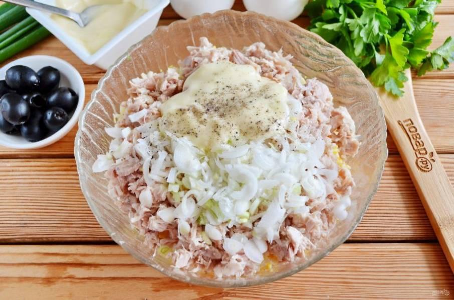 У зеленого лука отрежьте белые части, они более нежные на вкус, чем репчатый лук, порежьте тонко полукольцами. Добавьте в салат вместе с солью, перцем и майонезом. Перемешайте салат.