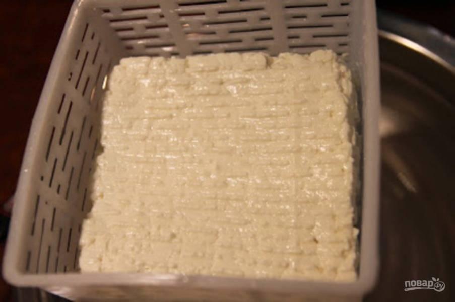 Через час слейте часть сыворотки, так чтобы остальная часть только немного покрывала сыр. Творог нагреваем до 37 градусов, постоянно перемешивая. Нам нужно, чтобы получилась зернистая текстура, чтобы при надавливании он слегка пружинил.  Полученный таким образом творог отбросьте на дуршлаг. Дайте стечь жидкости с одной стороны и с другой по часу.
