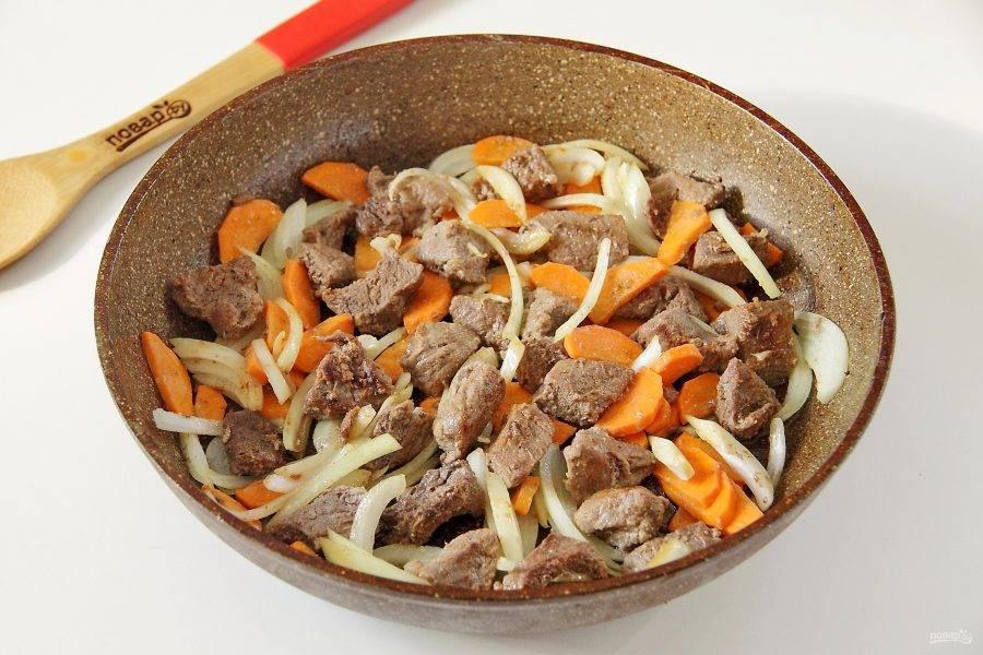 Как только мясо подрумянится, добавьте к нему лук и морковь. Перемешайте и обжарьте говядину с морковью и луком до мягкости овощей.