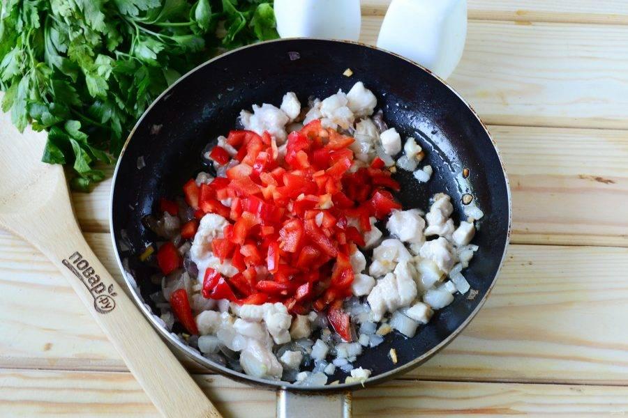 Сладкий перец очистите от семян и ополосните. Порежьте перец некрупным кубиком и также отправьте в сковороду, все перемешайте и готовьте на медленном огне 15-20 минут до мягкости всех овощей и готовности курицы.