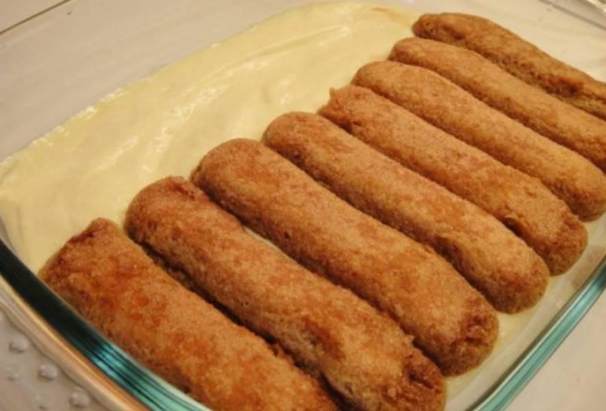 В прямоугольную высокую форму выкладываем слой крема. Печенье обмакиваем в свежезаваренный кофе и выкладываем вторым слоем.