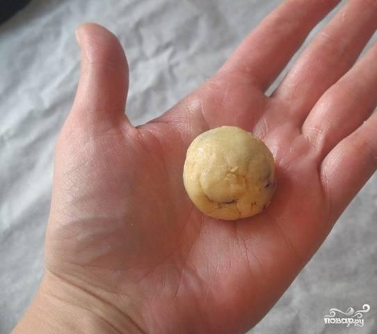 Готовое тесто поставьте в хлодильник на полчаса. Затем достаньте и скатайте шарики. Выложите все печеньки на застеленный пергаментом противень.