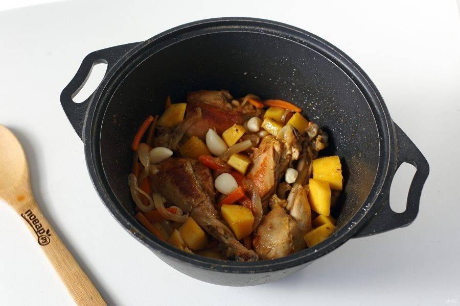 Добавьте нарезанную крупными кубиками тыкву, прогрейте мясо с овощами пару минут и разложите сверху очищенные зубчики чеснока.