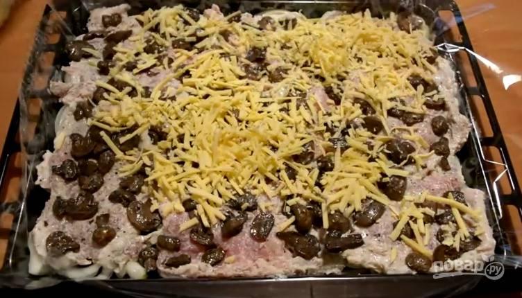 7. На лук выложите мясо в один слой, сверху — грибы, а последним слоем сыр. Запекайте при температуре 190-200 градусов 50-60 минут, до золотистой корочки.