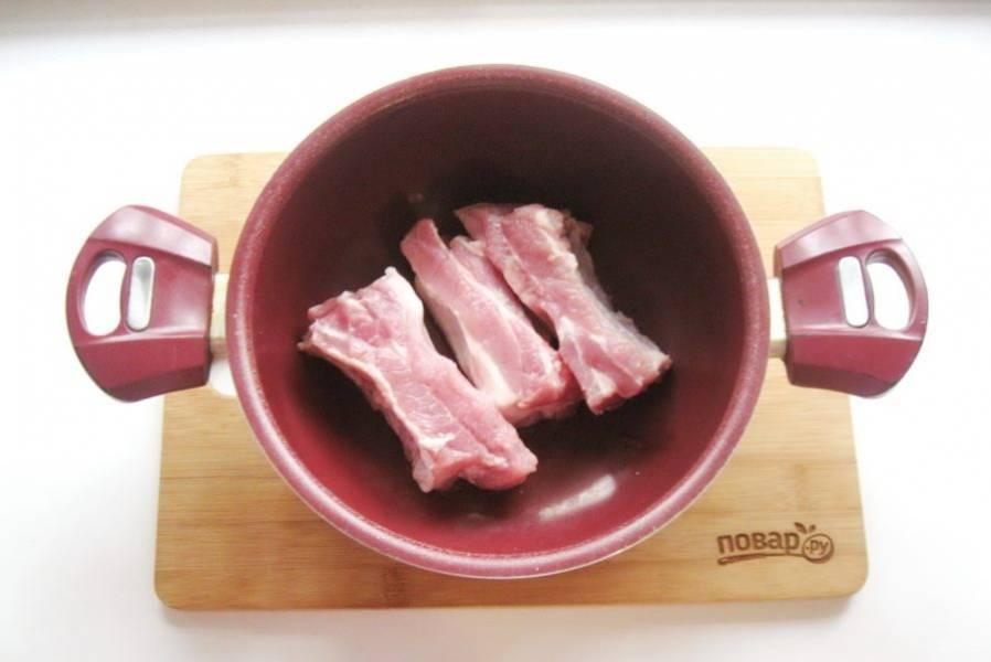 Свиные ребрышки помойте, обсушите и выложите в кастрюлю с толстым дном.