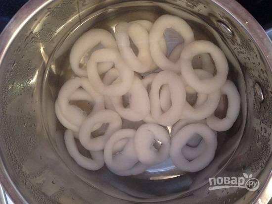 В первую очередь сварим кальмаров. Я чаще всего использую замороженные кольца кальмаров, с ними меньше возни. Бросаем кольца в кипящую воду и варим 3 минуты.