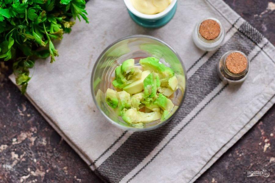 Далее возьмите авокадо, выберите мягкий и спелый. Очистите авокадо и нарежьте небольшими кубиками, выложите поверх кальмаров.