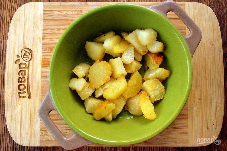 Картофель очистите, нарежьте кубиками и обжарьте на растительном масле до золотистой корочки. Выложите его в форму для запекания.