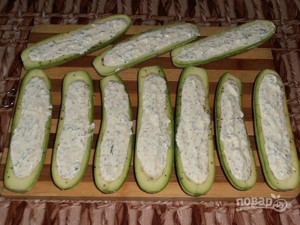 Заполняем кабачковые лодочки творожной начинкой.