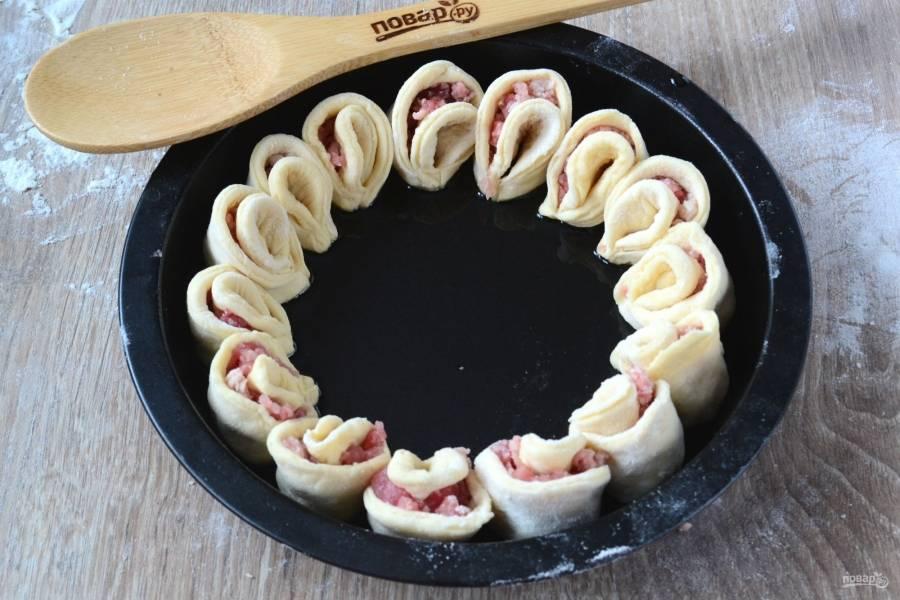 Полученные заготовки сложите в круглую форму для выпечки сначала по большом кругу.
