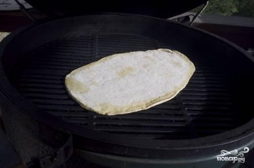Положите готовую для запекания основу в духовку или на гриль, предварительно нагрев ее до 200-230 градусов. Если готовите пиццу на гриле, кладите маслом вниз, если же в духовке – маслом вверх, но не забудьте дополнительно смазать противень.
