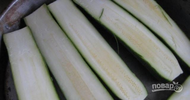 Кабачки хорошенько вымойте, обрежьте их с обеих сторон. Очищать от кожуры не надо. Разрежьте каждый овощ на две части. Выбирайте молодые кабачки, они нежные и вкусные. Также вы можете использовать цукини.