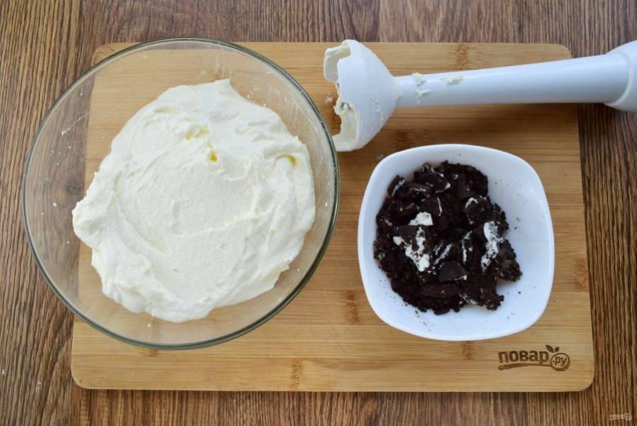 Творог пробейте блендером до однородной массы, добавьте сахар, ванилин, размягченное сливочное масло, йогурт пробейте блендером. Печенье поломайте на мелкие кусочки.