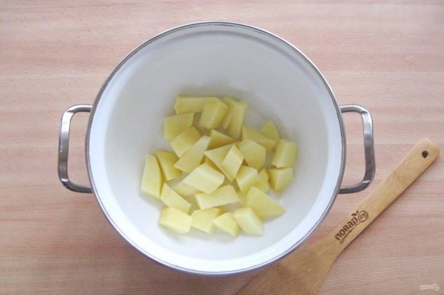 Картофель очистите, помойте и нарежьте. Выложите в кастрюлю.