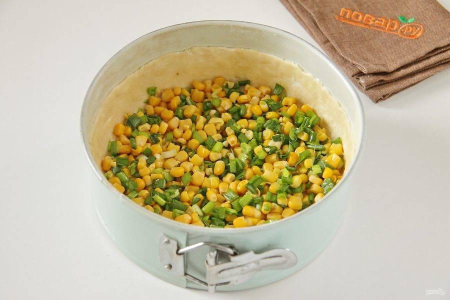 7. Соедините кукурузу, предварительно слив с нее жидкость, и нарезанный зеленый лук. Добавьте немного соли, перец по желанию, перемешайте и выложите равномерно на тесто.