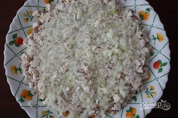 2. Очистите и измельчите луковицу. Можно ошпарить лук кипятком, замариновать его в уксусе или в соке лимона, например. Выложите поверх курицы.